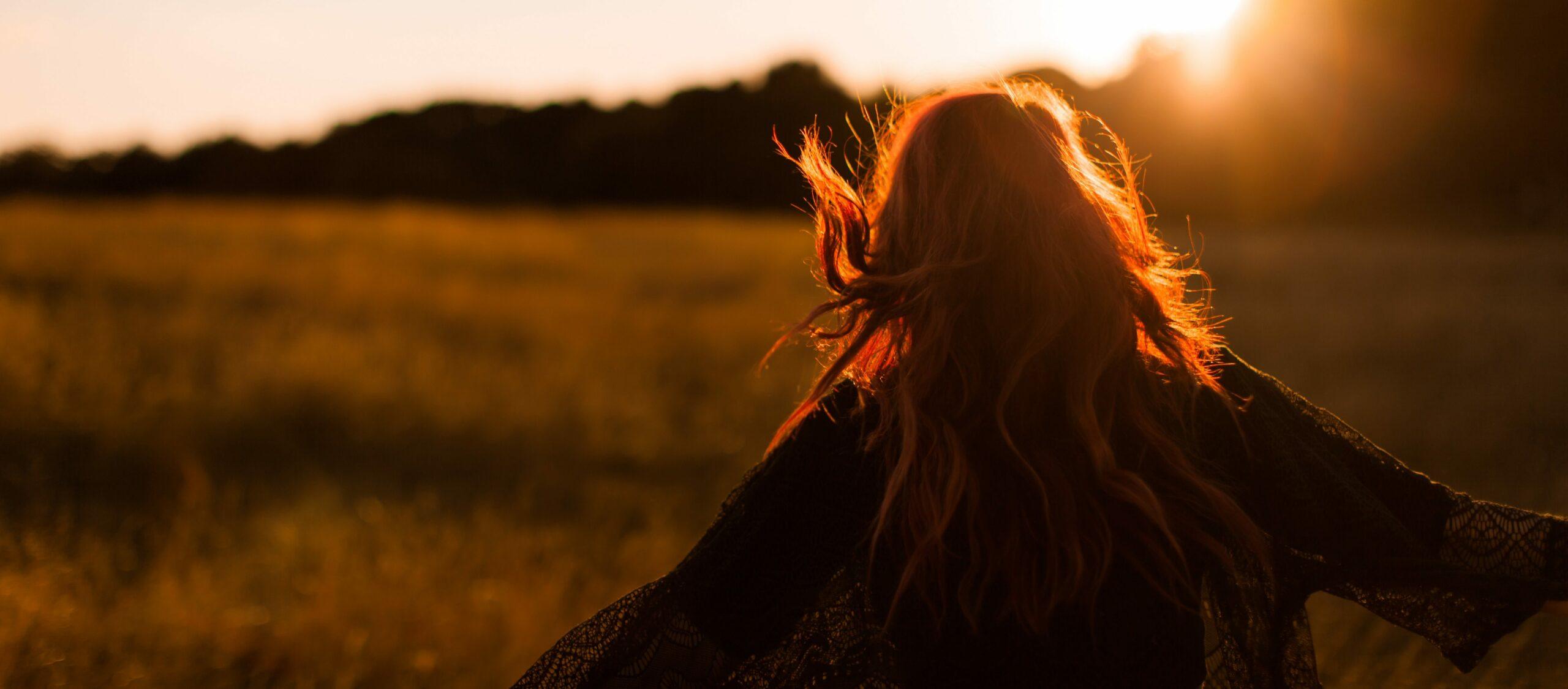 fille debout dans un champ au coucher du soleil