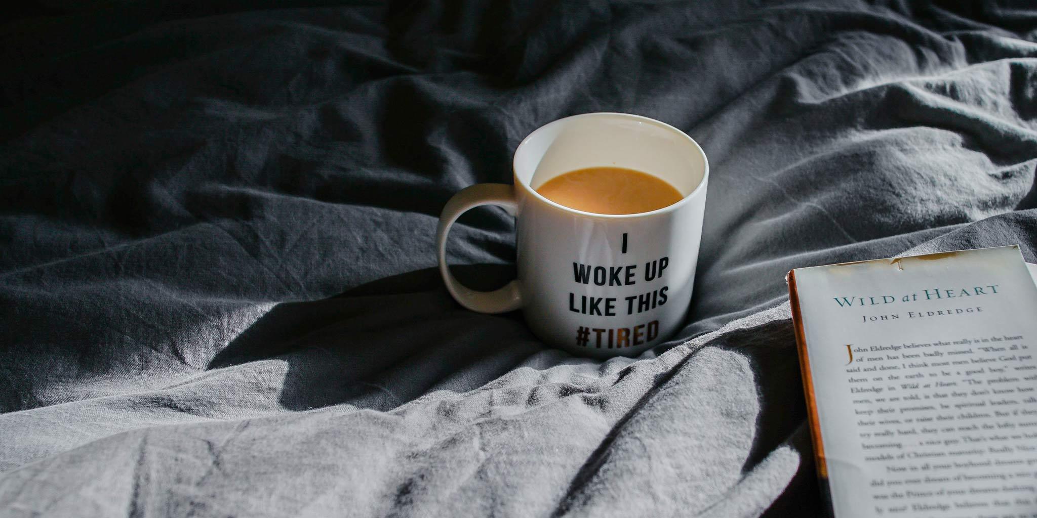 Koffie in een mok met een boek op een bed
