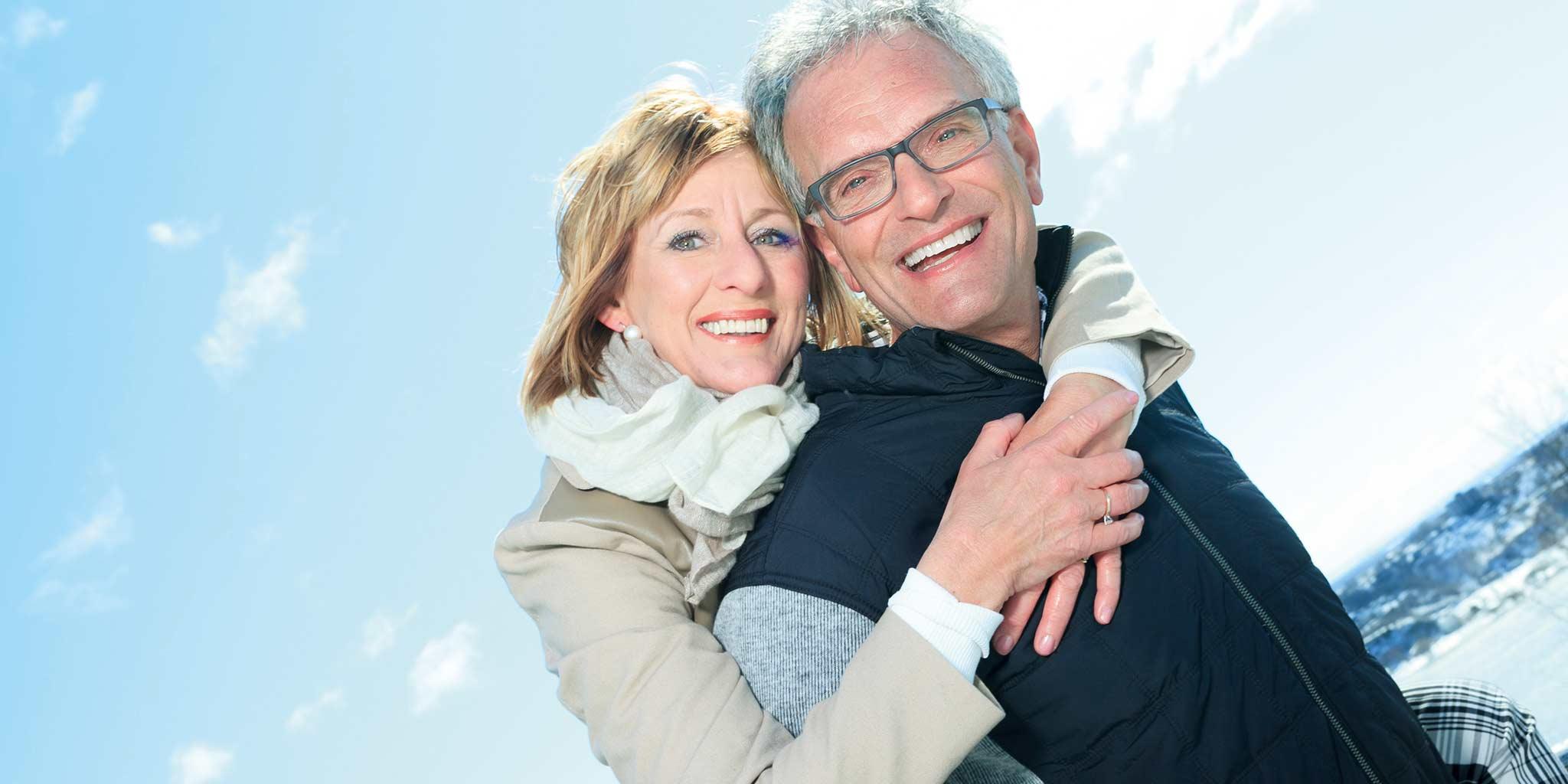 Vrouw omhelst man met een bril en kijken lachend naar de camera