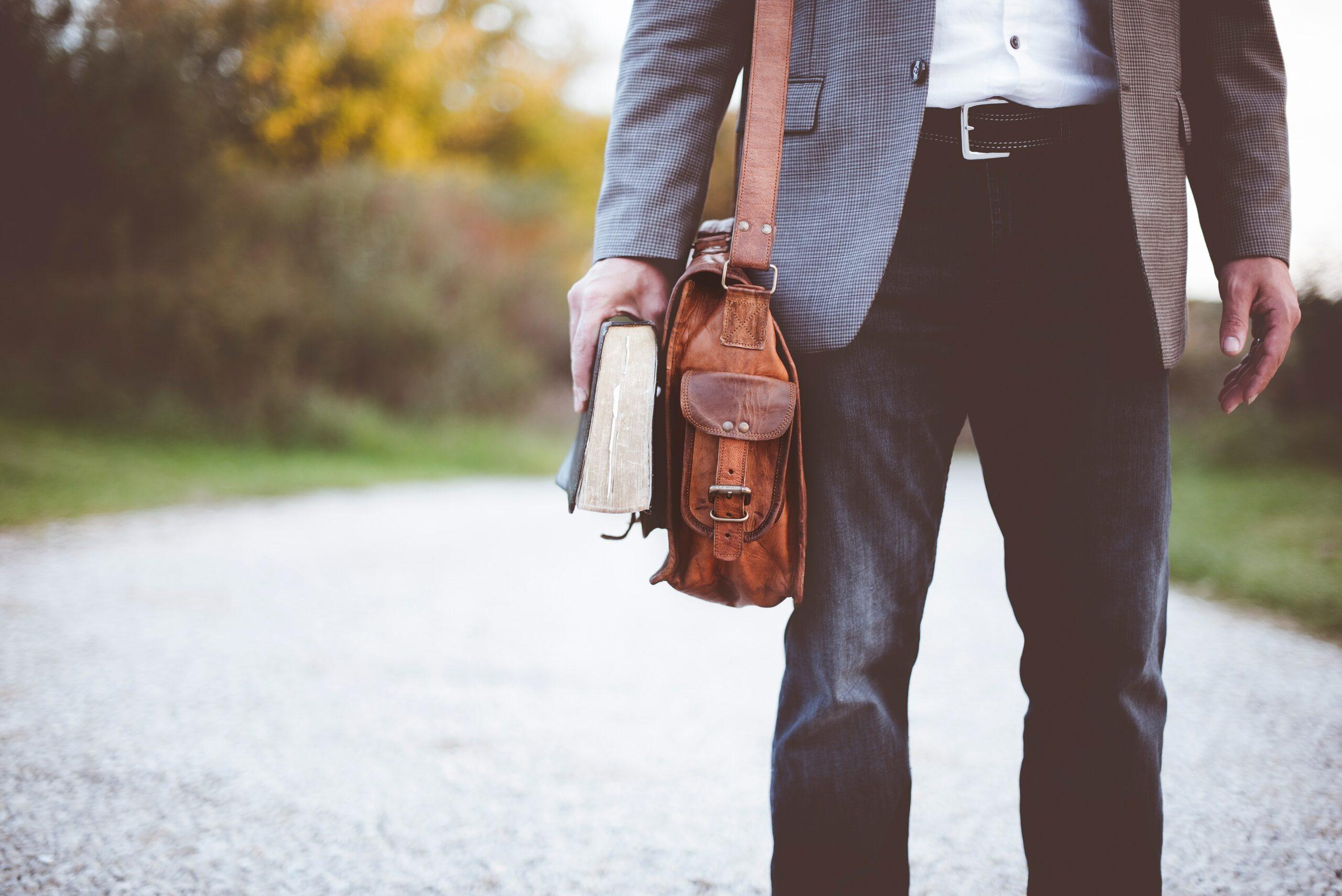 homme tenant un livre et un sac en cuir
