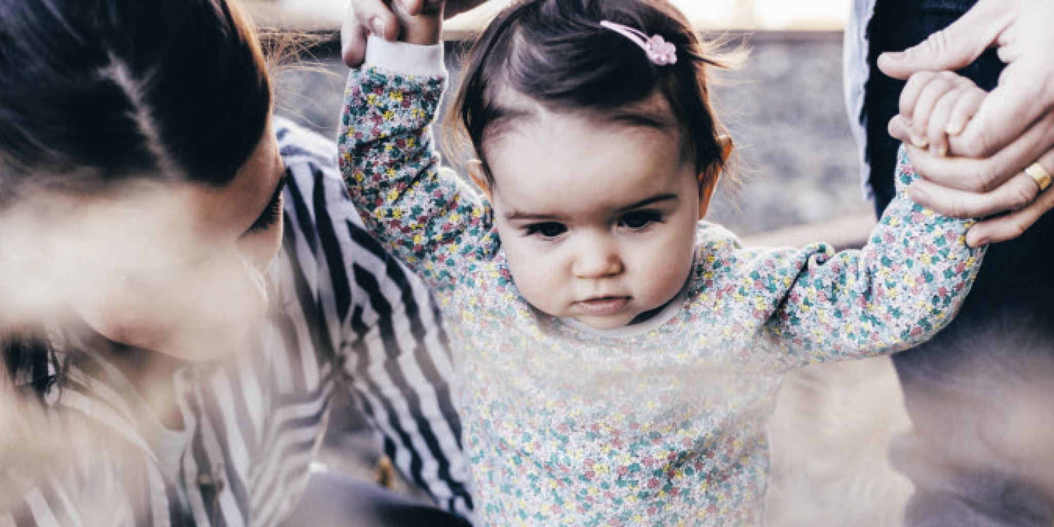 un bébé avec les mains en l'air tenu par un parent