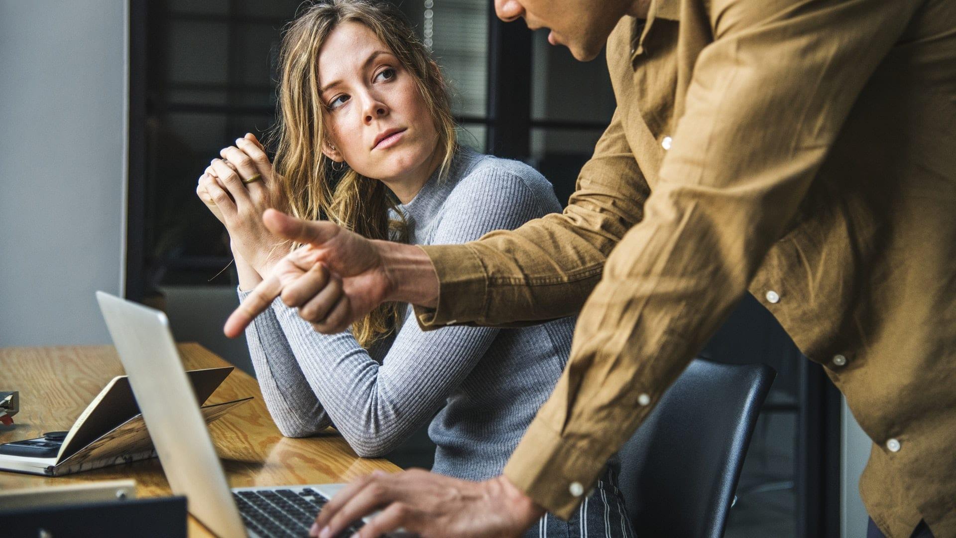 Man en vrouw kijken naar elkaar terwijl de man wijst naar de scherm van een laptop