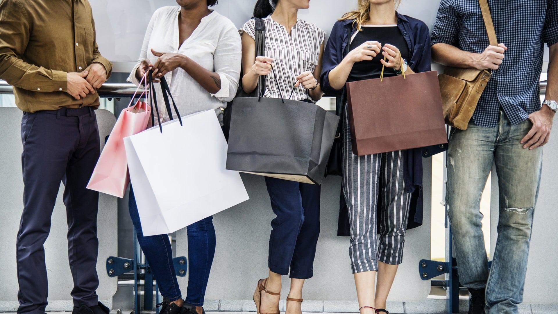Vrouwen met een shoppingbags en mannen die ernaast staan