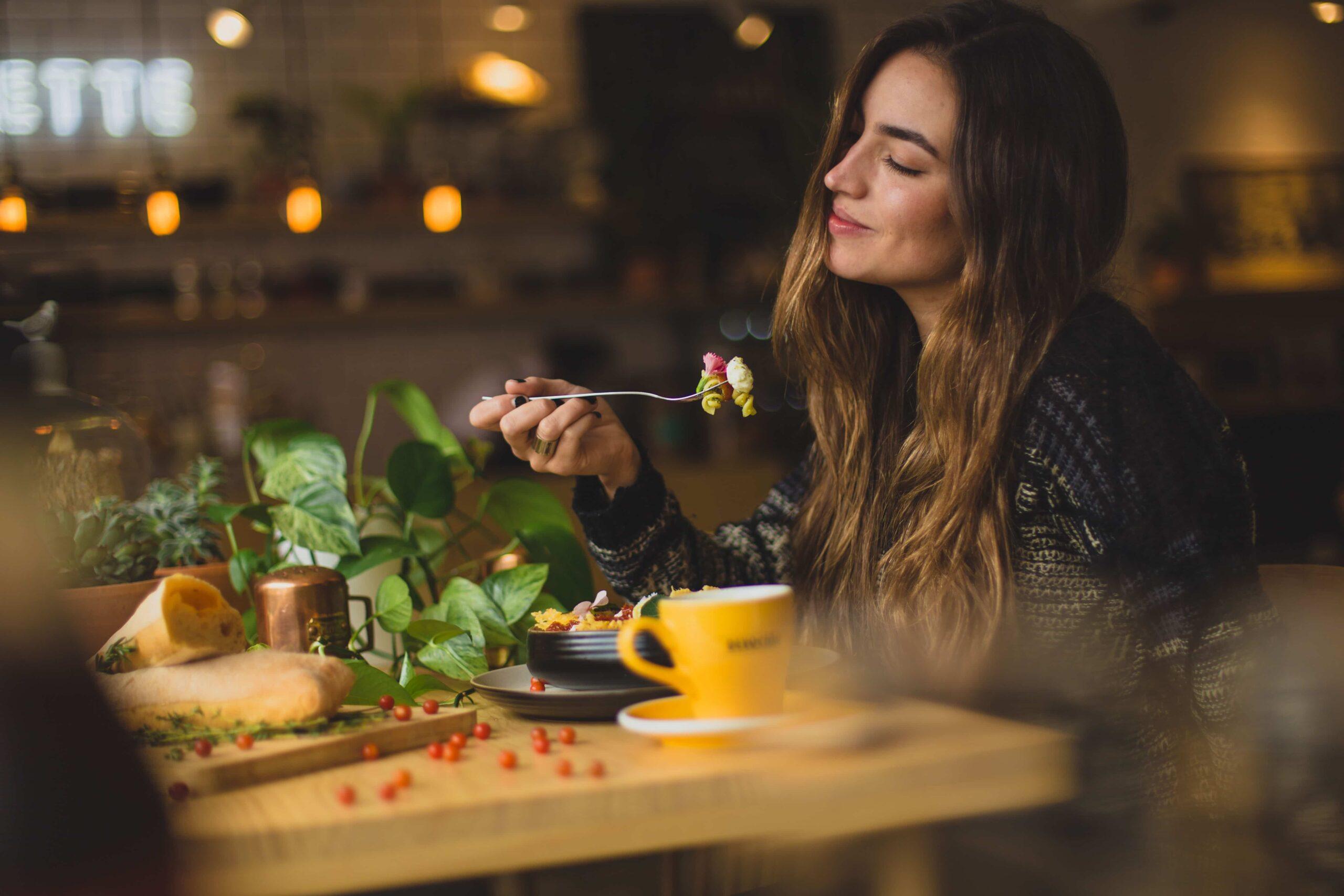 Vrouw zit aan een tafel en is aan het genieten van haar eten